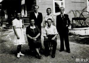 Fotografia biało-czarna. Przed domem grupa osób pozuje do zdjęcia