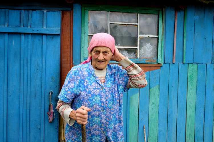 starsza kobieta w chustce przed drewnianym domem